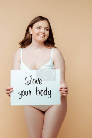 Foto de Cheerful plus size woman holding placard with love your body lettering isolated on beige, body positive concept. - Imagen libre de derechos
