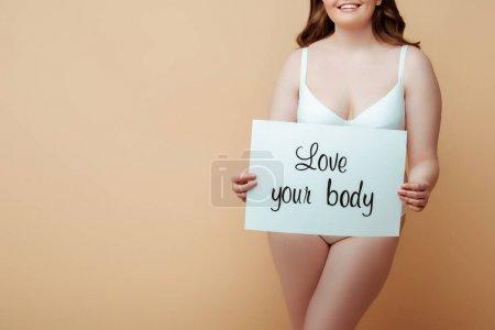 Foto de Vista recortada de la mujer sonriendo y presentando pancarta con amor su cuerpo letras sobre fondo beige - Imagen libre de derechos