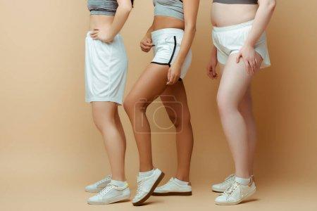 Foto de Vista recortada de deportistas multiculturales en pantalones cortos en beige - Imagen libre de derechos