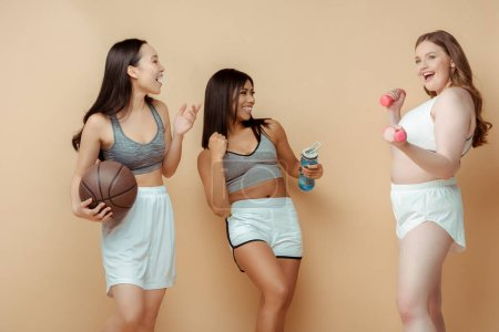 Photo for Multicultural sportswomen with ball, sports bottle and dumbbells smiling and looking at each other on beige - Royalty Free Image