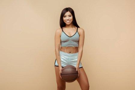 Photo pour Vue de face de la belle sportive afro-américaine souriante, tenant le ballon et regardant la caméra isolée sur beige - image libre de droit