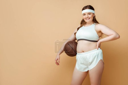 Photo for Plus size sportswoman with ball and hand on hip smiling and looking at camera on beige - Royalty Free Image