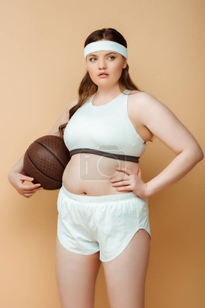 Photo for Plus size sportswoman with hand on hip looking away and holding ball on beige background - Royalty Free Image