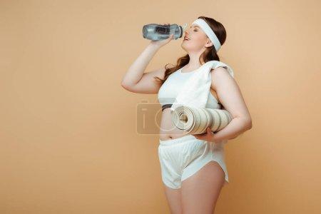 Photo pour Plus taille sportive avec tapis de fitness eau potable sur beige - image libre de droit