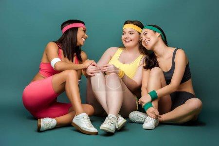 Photo pour Sportives multiethniques assis avec les jambes croisées, souriant et se regardant sur le vert - image libre de droit
