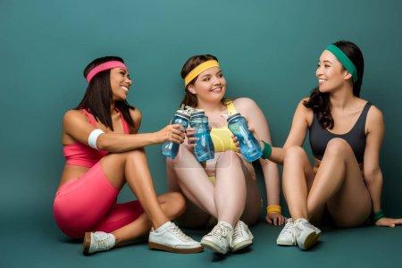 Photo pour Sportives multiethniques assis avec les jambes croisées, souriant, tenant des bouteilles de sport et se regardant sur le vert - image libre de droit