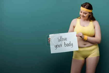 Foto de Además tamaño deportista sonriendo y mirando cartel con amor su cuerpo letras en verde - Imagen libre de derechos