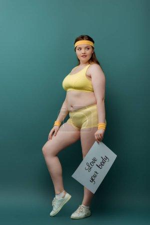 Photo pour Plus taille sportive avec pancarte avec amour votre lettrage de corps regardant loin sur fond vert - image libre de droit
