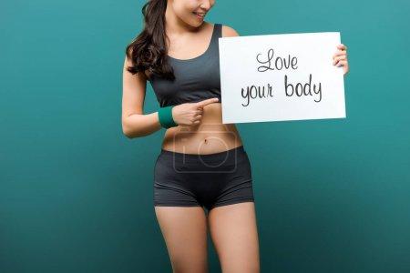Photo pour Vue recadrée de la sportive souriante et pointant vers la plaque avec amour votre lettrage de corps sur fond vert - image libre de droit