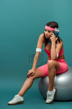 Photo pour Sportive africaine américaine réfléchie avec bouteille de sport sur balle de fitness sur fond vert - image libre de droit