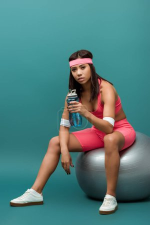 Attractive african american sportswoman holding sports bottle and looking at camera on fitness ball on green background