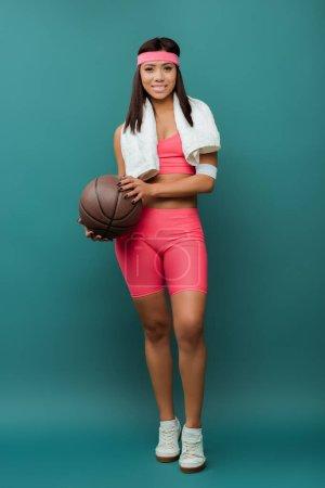 Photo pour Femme sportive afro-américaine souriante et regardant la caméra avec serviette et balle sur vert - image libre de droit