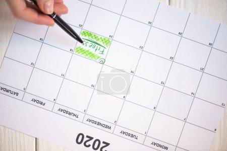 Photo pour Vue croustillante d'une femme pointant avec un stylo sur du lettrage de conditionnement physique dans un calendrier à faire avec inscription 2020 sur fond en bois - image libre de droit