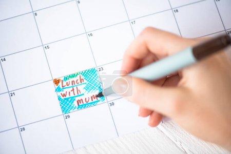 Photo pour Vue croustillante d'une femme pointant à l'aide d'un stylo-feutre au déjeuner avec lettres de la mère dans un calendrier à faire sur fond de bois - image libre de droit