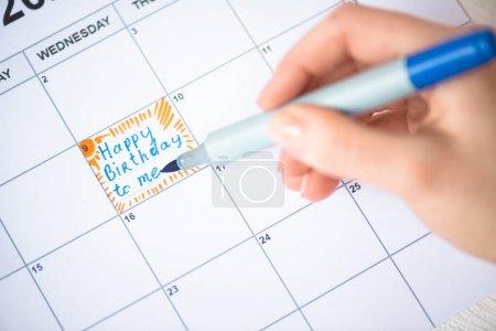Photo pour Vue agrandie de la femme pointant avec un stylo marqueur sur joyeux anniversaire à moi en lettres dans le calendrier à faire - image libre de droit