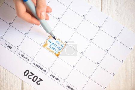 Photo pour Vue croustillante d'une femme pointant avec un stylo à l'occasion d'un joyeux anniversaire à moi en lettres dans un calendrier à faire avec inscription 2020 sur fond en bois - image libre de droit