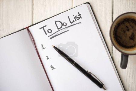 Photo pour Vue du dessus du carnet avec liste de choses à faire lettrage et stylo près de tasse de café sur fond en bois - image libre de droit