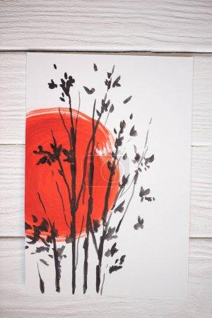 Photo pour Vue du dessus du papier avec peinture japonaise avec soleil rouge et branches sur fond en bois - image libre de droit