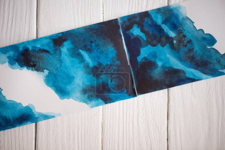 Photo for Top view of pictures with Japanese painting with blue watercolor on wooden background - Royalty Free Image