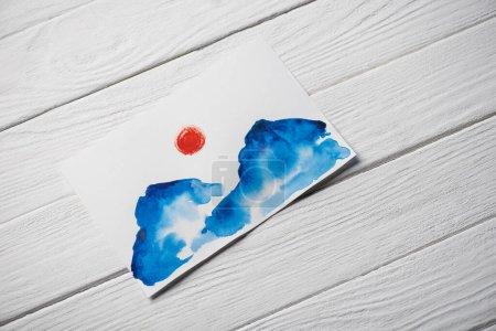 Photo pour Vue du dessus du papier avec peinture japonaise avec nuages et soleil sur fond en bois - image libre de droit