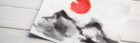 Vue du dessus du papier avec peinture japonaise avec collines et soleil rouge sur fond en bois, vue panoramique