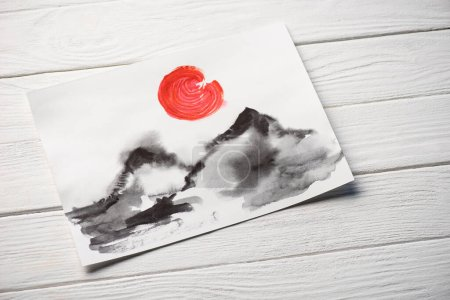 Photo for Top view of paper with Japanese painting with hills and red sun on wooden background - Royalty Free Image