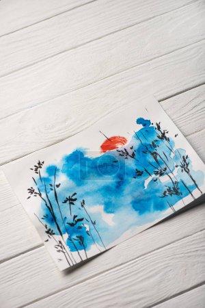 Photo pour Vue à grand angle de papier avec peinture japonaise avec ciel, branches et soleil sur fond de bois - image libre de droit
