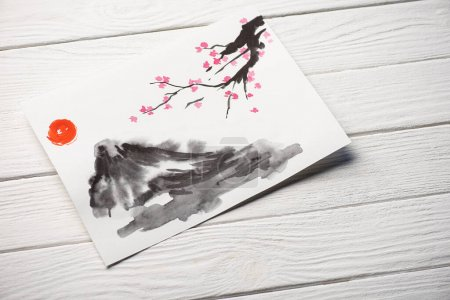 Photo for High angle view of paper with japanese painting with sun, Sakura branches and grey hill on wooden background - Royalty Free Image