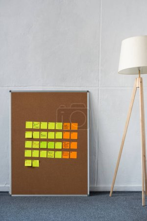 Photo for Brown board with yellow and orange sticky notes with floor lamp near wall - Royalty Free Image