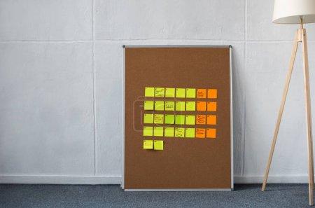 Photo pour Tableau brun avec des notes collantes jaunes et orange et un lampadaire près du mur - image libre de droit