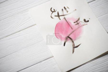 Foto de Vista de gran angular del papel con pintura japonesa con jeroglíficos en círculo rosa sobre fondo de madera. - Imagen libre de derechos