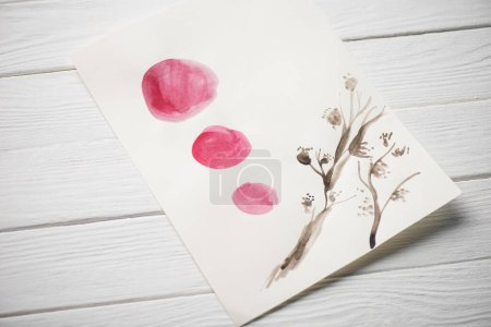 Photo for High angle view of paper with japanese painting with plant and pink circles on wooden background - Royalty Free Image