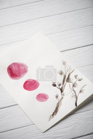 Foto de Vista de gran angular del papel con pintura japonesa con plantas y círculos sobre fondo de madera. - Imagen libre de derechos