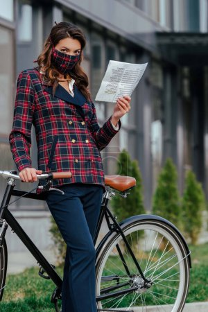 businesswoman in plaid mask holding newspaper near bicycle