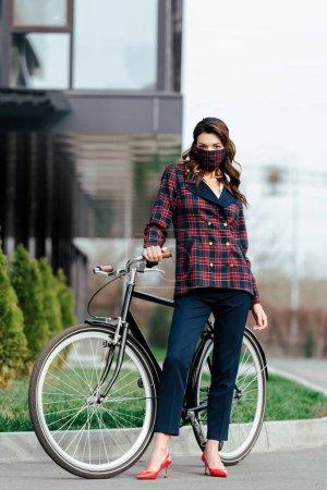 femme d'affaires en masque à carreaux debout près du vélo