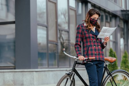 businesswoman in plaid mask standing near bicycle and reading newspaper