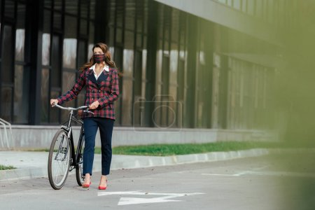 selective focus of businesswoman in plaid mask walking with bicycle