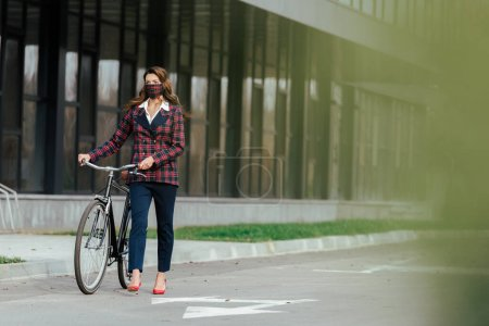 foyer sélectif de la femme d'affaires en masque à carreaux marche avec vélo