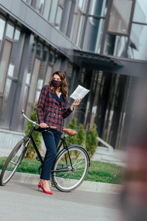 Photo for Selective focus of businesswoman in plaid mask holding newspaper and standing near bicycle - Royalty Free Image