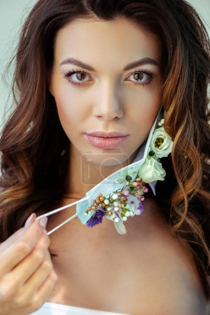 Photo for Attractive woman touching face mask with flowers and looking at camera isolated on grey - Royalty Free Image