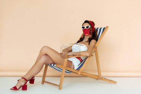 Photo pour Fille élégante en lunettes de soleil, masque et maillot de bain assis sur la chaise longue sur beige - image libre de droit