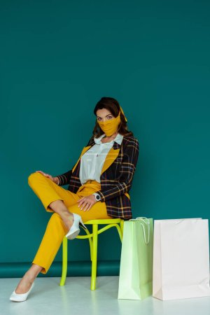 Photo pour Femme élégante en masque jaune et blazer à carreaux posant tout en étant assis sur la chaise près de sacs à provisions sur bleu - image libre de droit