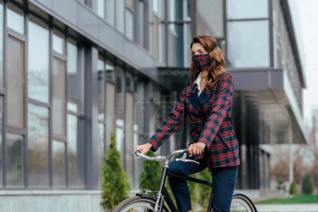 businesswoman in plaid mask riding bicycle outside