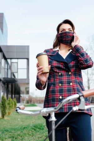 Geschäftsfrau in karierter Maske mit Kaffee zum Fahrradfahren