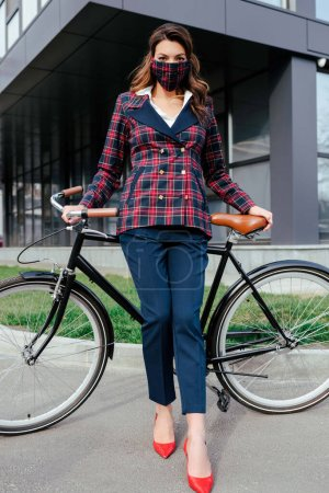 businesswoman in plaid mask standing near bicycle and building