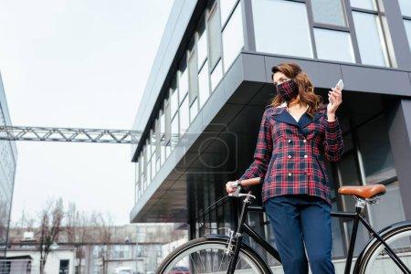 mujer de negocios en la máscara de cuadros de pie cerca de la bicicleta con teléfono inteligente
