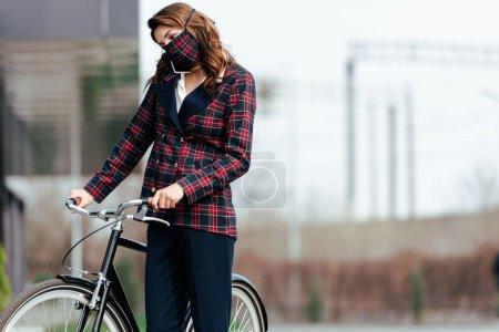Photo pour Femme d'affaires en plaid masque parler sur smartphone près de vélo à l'extérieur - image libre de droit