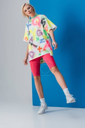 Photo for Beautiful woman posing in neon pink bike shorts and colorful t-shirt on grey and blue - Royalty Free Image