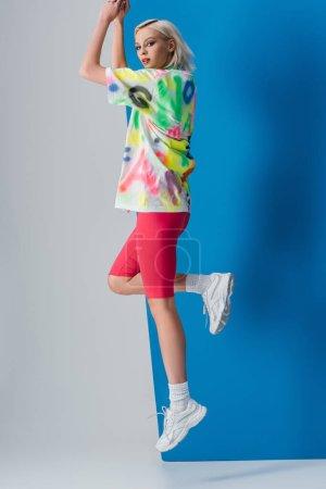 Photo pour Jolie jeune fille sautant en shorts de vélo rose néon et t-shirt coloré sur gris et bleu - image libre de droit