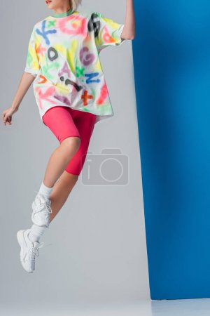 Photo for Fashionable woman jumping in neon pink bike shorts and colorful t-shirt on grey and blue - Royalty Free Image